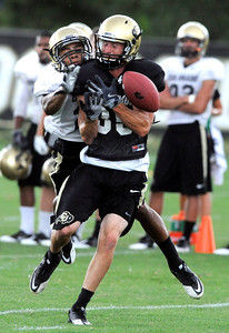 Greg Henderson, 20, breaks up a pass intended for Ryan Deehan, 35, during the University of Colorado afternoon practice on the Boulder Campus on Tuesday. FOR MORE PHOTOS A VIDEO INTERVIEW FROM THE PRACTICE GO TO WWW.DAILYCAMERA.COM Photo by Paul Aiken / The Camera / 8/ 16/ 11