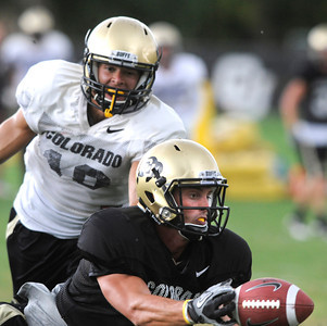 Logan Gray, 2, makes a fingertip catch in front of Travis Sandersfeld, 19, during the University of Colorado afternoon practice on the Boulder Campus on Tuesday. FOR MORE PHOTOS A VIDEO INTERVIEW FROM THE PRACTICE GO TO WWW.DAILYCAMERA.COM Photo by Paul Aiken / The Camera / 8/ 16/ 11