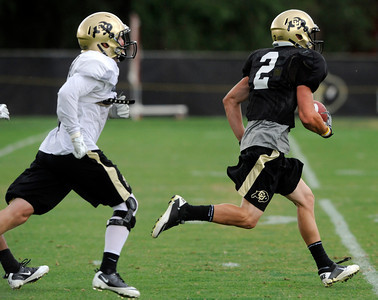 Logan Gray, 2, runs away from Parker Orms, 13, after making a catch during the University of Colorado afternoon practice on the Boulder Campus on Tuesday. FOR MORE PHOTOS A VIDEO INTERVIEW FROM THE PRACTICE GO TO WWW.DAILYCAMERA.COM Photo by Paul Aiken / The Camera / 8/ 16/ 11