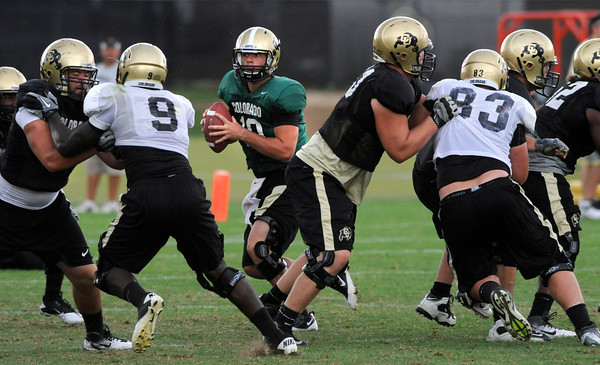 "Quarterback Brent Burnette, 10, drops back to pass as David Clark, 60, blocks Will Pericak, 83, during the University of Colorado afternoon practice on the Boulder Campus on Tuesday. FOR MORE PHOTOS A VIDEO INTERVIEW FROM THE PRACTICE GO TO  <a href=""http://WWW.DAILYCAMERA.COM"">http://WWW.DAILYCAMERA.COM</a><br /> Photo by Paul Aiken / The Camera / 8/ 16/ 11"