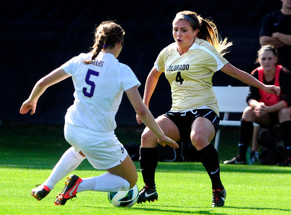 "University of Colorado Womens Team Soccer player Madison Krauser  (4) fights for the ball against Washington's Allyson Brahs (5) during their game in Boulder on Friday September 28, 2012. Photo by Paul Aiken /   <a href=""http://www.buffzone.com"">http://www.buffzone.com</a>"