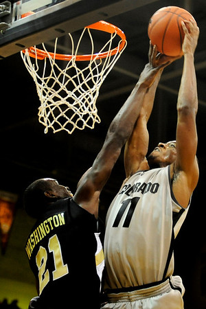 Colorado Buffalo's Cory Higgins (11) dunks over Arkansas-Pine Bluff's Tavaris Washington (21) during the season opener at the Coors Even Center in Boulder, Friday, Nov. 13, 2009. <br /> <br /> KASIA BROUSSALIAN / THE CAMERA