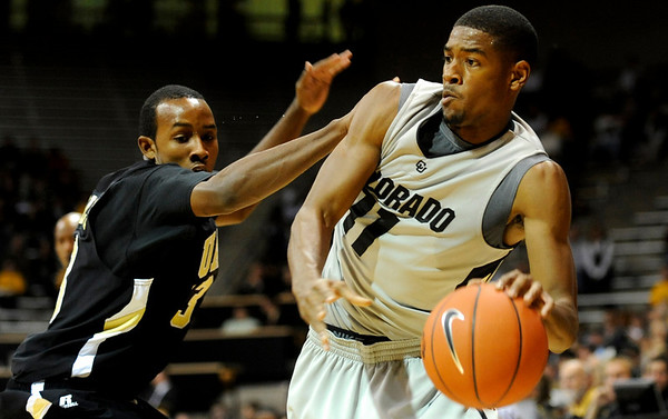 Colorado Buffalo's Cory Higgins (11) looks for an opening to the basket as Arkansas-Pine Bluff's Shane Stephan Collins (13) defends during the season opener at the Coors Even Center in Boulder, Friday, Nov. 13, 2009. <br /> <br /> KASIA BROUSSALIAN / THE CAMERA