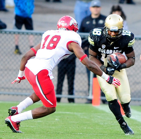 University of Colorado's Donta Abron runs the ball as Eric Rowe goes to tackle him during their game against Utah on Folsom Field in Boulder on Friday Nov. 23, 2012. DAILY CAMERA/ JESSICA CUNEO.