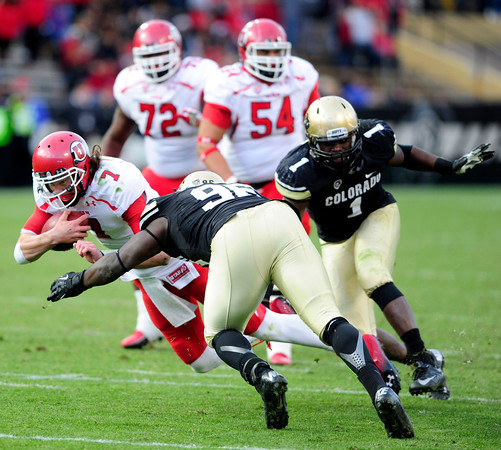 University of Colorado's Chidera Uzo-Diribe (96) and Derrick Webb (1) tackle Travis Wilson (7) during their game against Utah on Folsom Field in Boulder on Friday Nov. 23, 2012. DAILY CAMERA/ JESSICA CUNEO.