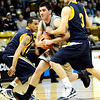 Colorado's Nate Tomlinson (center) gets past Colorado Christian's Anthony Urrutia (left) and Rye Olson (right) during their basketball game at the University of Colorado in Boulder, Colorado December 7, 2009.  CAMERA/Mark Leffingwell