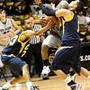 Colorado's Alec Burks (center) collides with Colorado Christian's Anthony Urrutia (right) and Joel Morris (left) during their basketball game at the University of Colorado in Boulder, Colorado December 7, 2009.  CAMERA/Mark Leffingwell