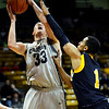 Colorado's Casey Crawford (left) is fouled by Colorado Christian's Anthony Urrutia (right) during their basketball game at the University of Colorado in Boulder, Colorado December 7, 2009.  CAMERA/Mark Leffingwell