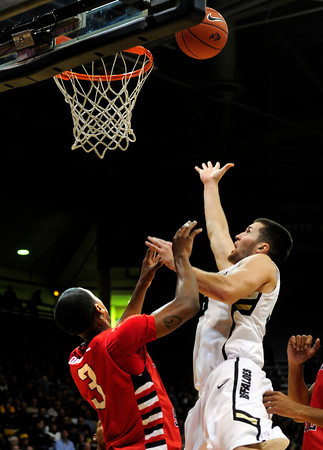 """Austin Dufault (33) of the University of Colorado Buffaloes drives of over Kevin Olekaibe (3) of the Fresno State Bulldogs during their game in Boulder Colo. on Wednesday December 7, 2011.   Photo by Paul Aiken / The Boulder Camera / December 7, 2011<br /> For more photos go to  <a href=""""http://www.buffzone.com"""">http://www.buffzone.com</a>"""