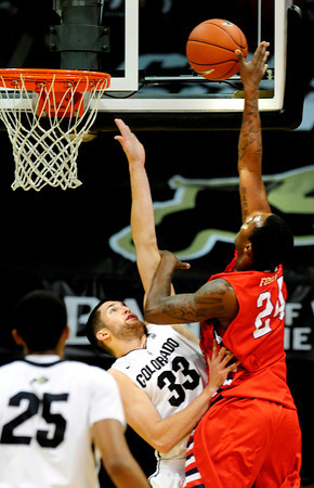 """The University of Colorado Buffalo Austin Dufault (33) tries to block a shot by Kevin Foster (24) of the Fresno State Bulldogs during their game in Boulder Colo. on Wednesday December 7, 2011.   Photo by Paul Aiken / The Boulder Camera / December 7, 2011<br /> For more photos go to  <a href=""""http://www.buffzone.com"""">http://www.buffzone.com</a>"""