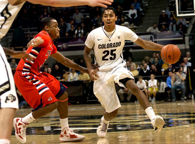 Spencer Dinwiddie (25) of the University of Colorado Buffaloes drives around Kevin Olekaibe (3) of the Fresno State Bulldogs during their game in Boulder Colo. on Wednesday December 7, 2011.   Photo by Paul Aiken / The Boulder Camera / December 7, 2011 For more photos go to www.buffzone.com