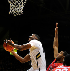 Jeremy Adams (31) of the University of Colorado Buffaloes shoots past  Jerry Brown (0) of the Fresno State Bulldogs during their game in Boulder Colo. on Wednesday December 7, 2011.   Photo by Paul Aiken / The Boulder Camera / December 7, 2011 For more photos go to www.buffzone.com
