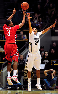 University of Colorado Buffalo Spencer Dinwiddie (25) tries to block a shot by Kevin Olekaibe (3) of the Fresno State Bulldogs during their game in Boulder Colo. on Wednesday December 7, 2011.   Photo by Paul Aiken / The Boulder Camera / December 7, 2011 For more photos go to www.buffzone.com