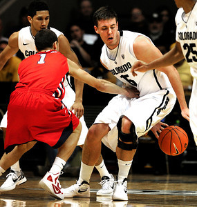 Shane Harris-Tunks (15)  of the University of Colorado Buffaloes dribbles behind his back to work around Tyler Johnson (1) of the Fresno State Bulldogs during their game in Boulder Colo. on Wednesday December 7, 2011.   Photo by Paul Aiken / The Boulder Camera /  For more photos go to www.buffzone.com