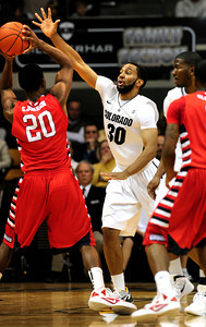 Carlon Brown (30) of the University of Colorado Buffaloes  guards Garrett Johnson (20) of the Fresno State Bulldogs during their game in Boulder Colo. on Wednesday December 7, 2011.   Photo by Paul Aiken / The Boulder Camera / December 7, 2011 For more photos go to www.buffzone.com