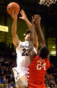 Sabatino Chen, (23) of the University of Colorado Buffaloes goes up against Kevin Foster (24) of the Fresno State Bulldogs during their game in Boulder Colo. on Wednesday December 7, 2011.   Photo by Paul Aiken / The Boulder Camera / December 7, 2011 For more photos go to www.buffzone.com