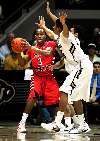 """Spencer Dinwiddie (25) of the University of Colorado Buffaloes guards Kevin Olekaibe (3) of the Fresno State Bulldogs during their game in Boulder Colo. on Wednesday December 7, 2011.   Photo by Paul Aiken / The Boulder Camera / December 7, 2011<br /> For more photos go to  <a href=""""http://www.buffzone.com"""">http://www.buffzone.com</a>"""