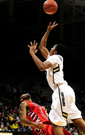 "Spencer Dinwiddie (25) of the University of Colorado Buffaloes shoots over Jerry Brown (0)  Fresno State Bulldogs during their game in Boulder Colo. on Wednesday December 7, 2011.   Photo by Paul Aiken / The Boulder Camera / December 7, 2011<br /> For more photos go to  <a href=""http://www.buffzone.com"">http://www.buffzone.com</a>"