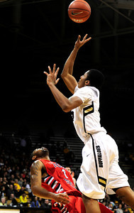 Spencer Dinwiddie (25) of the University of Colorado Buffaloes shoots over Jerry Brown (0)  Fresno State Bulldogs during their game in Boulder Colo. on Wednesday December 7, 2011.   Photo by Paul Aiken / The Boulder Camera / December 7, 2011 For more photos go to www.buffzone.com