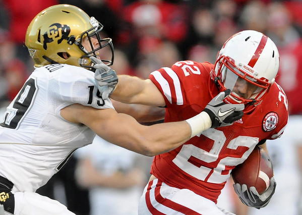 Nebraska running back Rex Burkhead (22) is challenged by Colorado safety Travis Sandersfeld (19) during the second half of of NCAA college football game, in Lincoln, Neb., Friday, Nov. 26, 2010. Burkhead passed for two touchdowns and ran for 101 yards and another score as Nebraska beat Colorado 45-17.  (AP Photo/Dave Weaver)