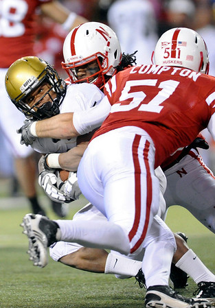 Colorado running back Rodney Stewart, left, is tackled by Nebraska defensive back DeJon Gomes, center, and linebacker Will Compton (51) in the second half of an NCAA college football game, in Lincoln, Neb., Friday, Nov. 26, 2010. Nebraska beat Colorado 45-17. (AP Photo/Dave Weaver)