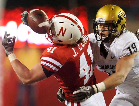 Nebraska tight end Jake Long (41) defended by Colorado safety Travis Sandersfeld (19) manages to hold on to a pass during the second half of an NCAA college football game, in Lincoln, Neb., Friday, Nov. 26, 2010. Nebraska beat Colorado 45-17. (AP Photo/Dave Weaver)