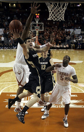Colorado guard Nate Tomlinson, right, from Australia, goes to the basket ahead of the defense by Texas center Dexter Pittman, left, during first half action in an NCAA college basketball game Saturday,  Jan. 9, 2010, in Austin, Texas. Colorado center Shane Harris-Tunks, (13) from Australia, along with Texas forward Damion James (5) look on.  (AP Photo/Harry Cabluck)