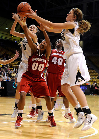 """University of Colorado's Julie Seabrook, left, fights for the rebound with Wisconsin's Jade Davis, No. 00, and Colorado's Rachel Hargis, right,  on Saturday, Nov. 26, during a basketball game against the University of Wisconsin at the Coors Event Center on the CU campus in Boulder. For more photos of the game go to  <a href=""""http://www.dailycamera.com"""">http://www.dailycamera.com</a><br /> Photo by Jeremy Papasso"""