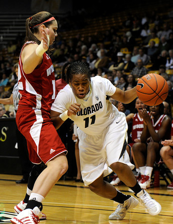 "University of Colorado's Brittany Wilson drives past Wisconsin's Lindsay Smith on Saturday, Nov. 26, during a basketball game against the University of Wisconsin at the Coors Event Center on the CU campus in Boulder. For more photos of the game go to  <a href=""http://www.dailycamera.com"">http://www.dailycamera.com</a><br /> Photo by Jeremy Papasso"
