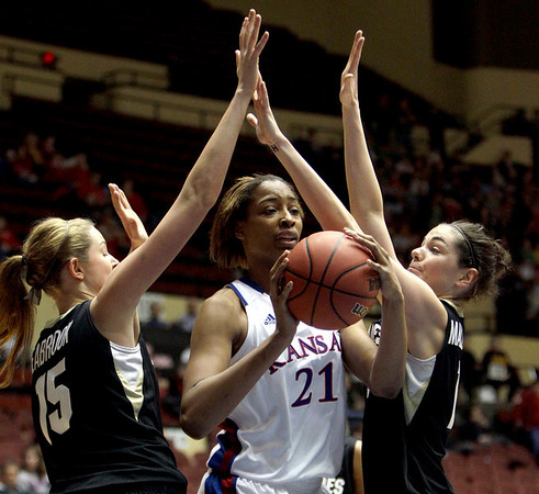 Kansas' Carolyn Davis, center, passes between Colorado defenders Julie Seabrook, left, and Meagan Malcolm-Peck during the first half of an NCAA college basketball game at the Big 12 Conference women's tournament on Tuesday, March 8, 2011, in Kansas City, Mo. (AP Photo/Jeff Roberson)