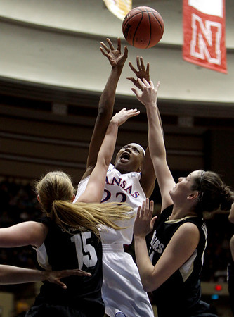 Kansas Marisha Brown, center, shoots over Colorado defenders Julie Seabrook, left, and Meagan Malcolm-Peck during the first half of an NCAA college basketball game at the Big 12 Conference women's tournament on Tuesday, March 8, 2011, in Kansas City, Mo. (AP Photo/Jeff Roberson)