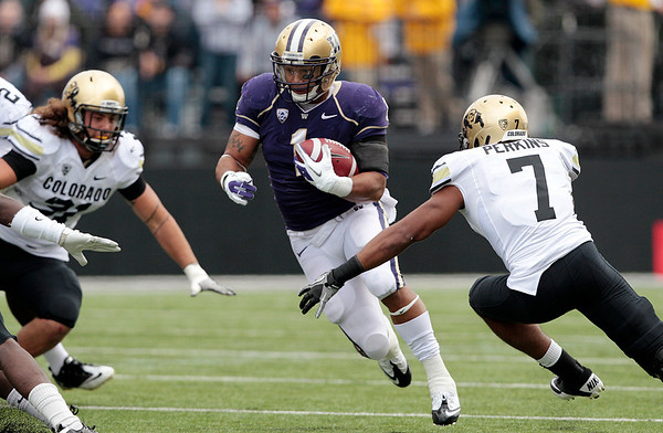 Washington's Chris Polk, center, runs against Colorado in the first half of an NCAA college football game, Saturday, Oct. 15, 2011, in Seattle. (AP Photo/Elaine Thompson)