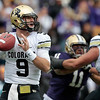 Colorado quarterback Tyler Hansen (9) looks for room to pass as David Goldberg, right, holds back Washington's Talia Crichton (11) in the first half of an NCAA college football game, Saturday, Oct. 15, 2011, in Seattle. (AP Photo/Elaine Thompson)