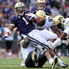 Washington's Chris Polk (1) is brought down by Colorado's Derrick Webb, bottom, Will Pericak (83) and Juda Parker, right, as he gains a first down late in the first half of an NCAA college football game, Saturday, Oct. 15, 2011, in Seattle. (AP Photo/Elaine Thompson)