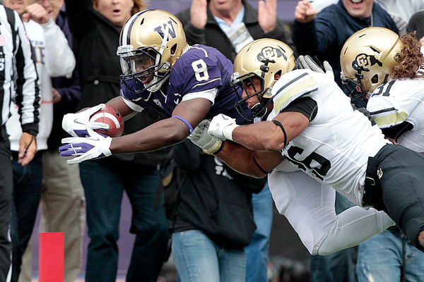 Washington's Kevin Smith (8) dives into the end zone on a 22-yard touchdown carry as Colorado's Tony Jones defends on in the first half of an NCAA college football game, Saturday, Oct. 15, 2011, in Seattle. (AP Photo/Elaine Thompson)