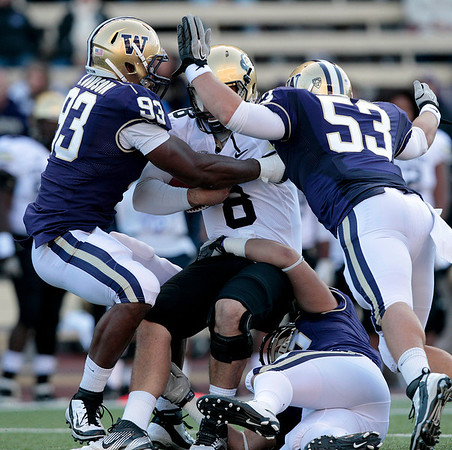Colorado quarterback Nick Hirschman is brought down by a trio of Washington defenders on a sack in the second half of an NCAA college football game, Saturday, Oct. 15, 2011, in Seattle. Washington won 52-24. (AP Photo/Elaine Thompson)