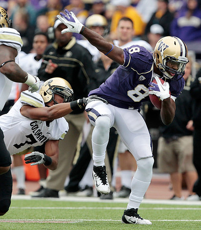 Washington's Kevin Smith (8) escapes a tackle attempt by Colorado's Anthony Perkins in the first half of an NCAA college football game, Saturday, Oct. 15, 2011, in Seattle. Washington won 52-24. (AP Photo/Elaine Thompson)