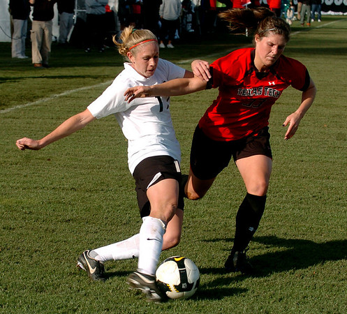 Nikki Marshall  of CU kicks toward the goal around Casey McCall of Texas Tech.<br /> Cliff Grassmick / October 30, 2009