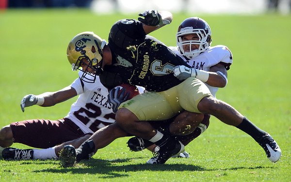 "Markquez Simas of CU  tries to pull away from the Texas A & M defenders.<br /> For more photos from the game, go to  <a href=""http://www.dailycamera.com"">http://www.dailycamera.com</a>.<br /> Cliff Grassmick / November 7, 2009"