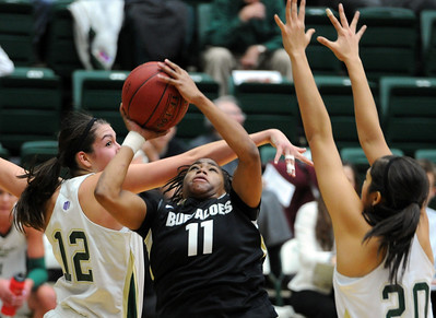 Brittany Wilson of CU, gets a shot under Sam Martin of CSU. For more photos of CU and CSU, go to www.dailycamera.com. November 20, 2011 / Cliff Grassmick