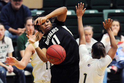 Brittany Wilson of CU, gets the ball knocked away by Meghan Heimstra, back, of CSU. For more photos of CU and CSU, go to www.dailycamera.com. November 20, 2011 / Cliff Grassmick