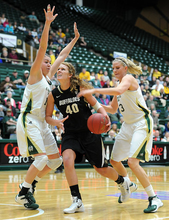 "Rachel Hargis of CU, drives between Sam Martin, and Kelly Hartig, both of CSU.<br /> For more photos of CU and CSU, go to  <a href=""http://www.dailycamera.com"">http://www.dailycamera.com</a>.<br /> November 20, 2011 / Cliff Grassmick"