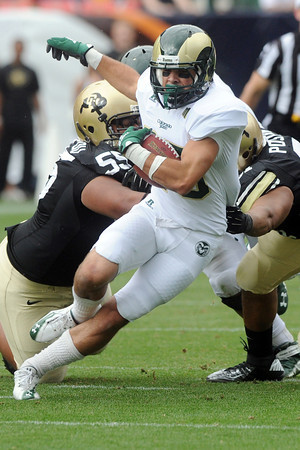 Colorado State's Joe Hansley runs up the middle between Colorado defenders Josh Tupou, left, and Kirk Poston in the first quarter of their game Saturday, Sept. 1, 2012 at Sports Authority Field at Mile High. (Steve Stoner/Loveland Reporter-Herald)