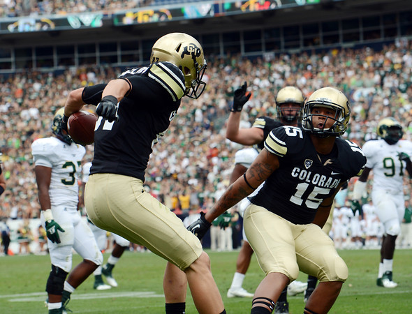 """Tyler McCulloch, left, and Vincent Hobbs of CU celebrate CU's second TD at the Rocky Mountain Showdown at Sports Authority Field in Denver on September 1, 2012.<br /> For more photos of the game, go to  <a href=""""http://www.dailycamera.com"""">http://www.dailycamera.com</a>.<br /> Cliff Grassmick / September 1, 2012"""