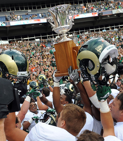 """The Colorado State Rams celebrate with the Centennial Cup after beating CU 22-17 at the Rocky Mountain Showdown at Sports Authority Field in Denver on September 1, 2012.<br /> For more photos of the game, go to  <a href=""""http://www.dailycamera.com"""">http://www.dailycamera.com</a>.<br /> Cliff Grassmick / September 1, 2012"""