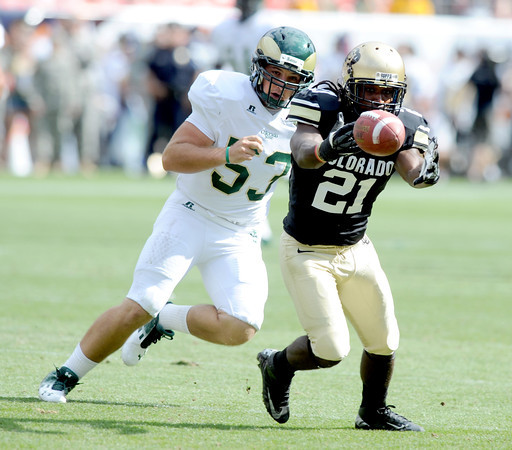 """D.D Goodson fumbles a punt return that CSU recovers during the first half of the Rocky Mountain Showdown at Sports Authority Field in Denver on September 1, 2012. Tanner Hedstrom of CSU is chasing.<br /> For more photos of the game, go to  <a href=""""http://www.dailycamera.com"""">http://www.dailycamera.com</a>.<br /> Cliff Grassmick / September 1, 2012"""