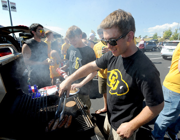 "CU student, Sal Rizzo, cooks up food for others in his group before the CU CSU game at Sports Authority Field in Denver on Saturday.<br /> For more photos of the game, go to  <a href=""http://www.dailycamera.com"">http://www.dailycamera.com</a>.<br /> Cliff Grassmick / September 1, 2012"