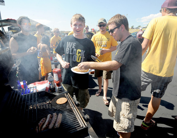 "CU student, Sal Rizzo, right,  cooks up food for Matt Abboud, center,  and others in his group before the CU CSU game at Sports Authority Field in Denver on Saturday.<br /> For more photos of the game, go to  <a href=""http://www.dailycamera.com"">http://www.dailycamera.com</a>.<br /> Cliff Grassmick / September 1, 2012"