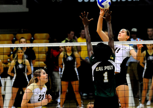 "CU Buff Rosie Steinhaus spikes the ball toward Cal Poly Mustang Dominique Olowolafe while CU Buff Kaitlyn Burkett, left, watches at the CU vs. Cal Poly volleyball game at CU-Boulder on Saturday, Sept. 12, 2009.  More photos at  <a href=""http://www.dailycamera.com"">http://www.dailycamera.com</a>."