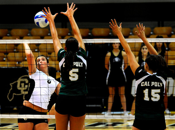 """CU Buff Nikki Kinzer spikes the ball while Cal Poly Mustangs Megan McConnell (5) and Megan McConnell (15) at the CU vs. Cal Poly volleyball game at CU-Boulder on Saturday, Sept. 12, 2009.  More photos at  <a href=""""http://www.dailycamera.com"""">http://www.dailycamera.com</a>."""